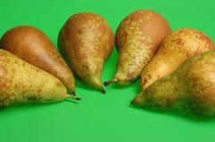 Varias peras en un fondo verde Foto de archivo