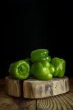Varias pimientas verdes frescas en un tocón de madera Foto de archivo libre de regalías