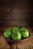 Varias pimientas verdes frescas en una arcilla arquean Fotos de archivo