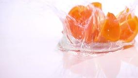 Varias rebanadas de naranja están cayendo en la tabla metrajes