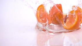 Varias rebanadas de naranja están cayendo en la tabla almacen de metraje de vídeo