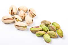 Varias tuercas de pistacho descubiertas y en el shell aislado Imagen de archivo libre de regalías