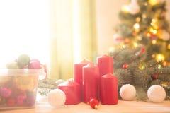 Varias velas rojas de la Navidad en el tablón de madera blanco contra el árbol de navidad en sala de estar Foto de archivo libre de regalías