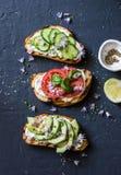 Variaties van sandwiches - met roomkaas, avocado, tomaat en komkommer op een donkere achtergrond, hoogste mening Conce van het ge royalty-vrije stock foto's