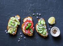 Variaties van sandwiches - met roomkaas, avocado, tomaat en komkommer op een donkere achtergrond, hoogste mening Conce van het ge stock afbeeldingen