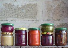 Variation av bevarad mat i exponeringsglaskrus - knipor, driftstopp, marmelad, såser, ketchup Bevara grönsaker och frukter jäst royaltyfri foto