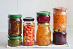 Variation av bevarad mat i exponeringsglaskrus - knipor, driftstopp, marmelad, såser, ketchup Bevara grönsaker och frukter jäst fotografering för bildbyråer