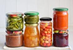 Variation av bevarad mat i exponeringsglaskrus - knipor, driftstopp, marmelad, såser, ketchup Bevara grönsaker och frukter jäst arkivbild