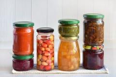 Variation av bevarad mat i exponeringsglaskrus - knipor, driftstopp, marmelad, såser, ketchup Bevara grönsaker och frukter jäst arkivfoton