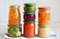 Variation av bevarad mat i exponeringsglaskrus - knipor, driftstopp, marmelad, såser, ketchup Bevara grönsaker och frukter jäst royaltyfria foton