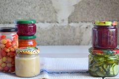 Variation av bevarad mat i exponeringsglaskrus - knipor, driftstopp, marmelad, såser, ketchup Bevara grönsaker och frukter Jäst f arkivbilder