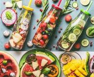Variation av den sunda detoxen ingav vatten med färgrika frukter, bär som smaksattes med nya örter, gurkan och citronen royaltyfri bild