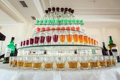 Variation av färgrika gula och röda alkoholskott för gräsplan i små exponeringsglas som står i rad på en glass ställning Arkivbilder