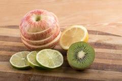 Variation av frukt som skivas på träskärbräda Arkivfoto