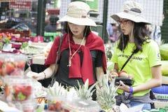 Variation av frukter på den till salu marknaden Persikor är ett magasin av vitaminer Shopparen väljer persikan på stadmarknad Royaltyfri Bild