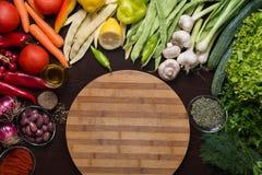 Variation av grönsaker och kryddor runt om skärbrädan Royaltyfria Bilder