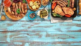 Variation av grillad mat på den blåa trätabellen Arkivfoto