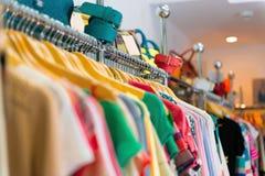 Variation av kläder som hänger på kuggen arkivbild