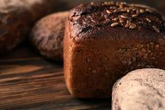 Variation av nytt smakligt bröd på trätabellen, closeup royaltyfria bilder
