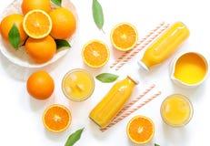 Variation av orange fruktsaft i flaskor och exponeringsglas, sugrör, apelsiner som isoleras på bästa sikt för vit bakgrund Royaltyfria Foton