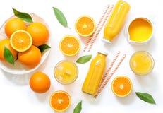 Variation av orange fruktsaft i flaskor och exponeringsglas, sugrör, apelsiner som isoleras på bästa sikt för vit bakgrund Royaltyfri Foto