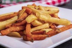 Variation av potatisar för garnering: franska småfiskar och sötpotatis på en platta royaltyfri bild