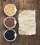 Variation av ris i bunkar på trätabellen och gammalt papper Fotografering för Bildbyråer