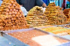 Variation av sötsaker på det arabiska gataståndet Östliga sötsaker i en lång räcka, baklava, turkisk fröjd med mandeln, kasju arkivfoto