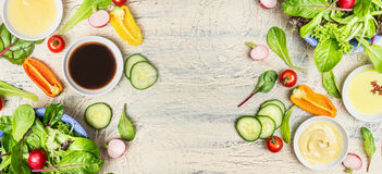 Variation av sunda sallad- och dressingingredienser på ljus lantlig bakgrund, bästa sikt, baner Arkivfoto