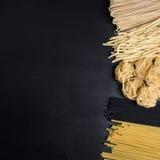 Variation av torr pasta för italienare på en svart bakgrund Bästa sikt, kopieringsutrymme Arkivbild