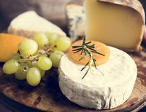 Variation of cheese and green grapes on a wooden platter food ph stock photo