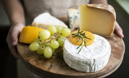 Variation of cheese and green grapes on a wooden platter food photography recipe idea stock photography