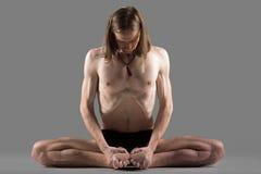 Variation of cobbler yoga pose. Sporty young man sitting in variation of goraksasana, baddha konasana posture (purna titli, bound angle, cobbler, butterfly pose Royalty Free Stock Photography