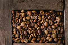 Variation of coffee beans. Food background with Green and brown decaf unroasted and black roasted coffee beans in old wooden box. Top view. Close up royalty free stock photography