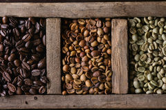 Variation of coffee beans. Food background with green and brown decaf unroasted and black roasted coffee beans in old wooden box. Top view. Close up stock photography