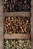 Variation of coffee beans. Food background with green and brown decaf unroasted and black roasted coffee beans in old wooden box. Top view. Close up stock image