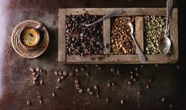 Variation of coffee beans. Green and brown decaf unroasted and black roasted coffee beans in old wooden box, and ceramic cup of fresh making coffee over dark royalty free stock images