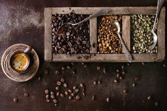 Variation of coffee beans. Green and brown decaf unroasted and black roasted coffee beans in old wooden box, and ceramic cup of fresh making coffee over dark stock photos