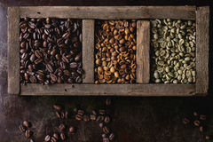 Variation of coffee beans. Green and brown decaf unroasted and black roasted coffee beans in old wooden box over dark brown textured background. Top view royalty free stock photos