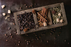 Variation of coffee beans. Green and brown decaf unroasted and black roasted coffee beans with spices and sugar cubes in old wooden box over dark brown textured stock images