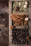 Variation of coffee beans. Green and brown decaf unroasted and black roasted coffee beans with spices and sugar cubes in old wooden box over dark brown textured stock photos