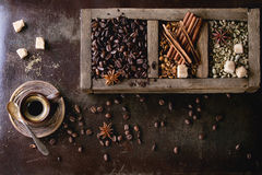 Variation of coffee beans. Green and brown decaf unroasted and black roasted coffee beans with spices and sugar in old wooden box, and ceramic cup of fresh stock images