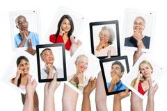 Variation des mains tenant des Tablettes de Digital avec les personnes ethniques multi pensant à l'inspiration Images stock