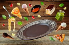 The variation of the flying Italian food and a brown plate on a Stock Photo