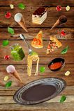 The variation of the flying Italian food and a brown plate on a Royalty Free Stock Photos