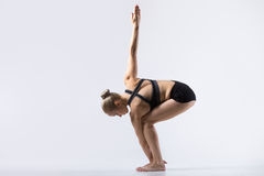 Variation of Parivrtta Utkatasana. Sporty beautiful young woman practicing yoga, doing Variation of Revolved Chair Pose, Parivrtta Utkatasana, working out Royalty Free Stock Photos