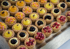 Variation of pastry decorated with various fruits Stock Photos