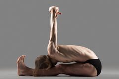 Variation of seated Forward Bend pose. Sporty muscular young yogi man sitting in variation of paschimottanasana, seated forward bend posture with arms stretched royalty free stock photo