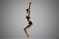 Variation of utkatasana yoga Pose. Beautiful young fit woman in sportswear doing sport exercise for shoulders, ankles, thighs, calves and spine, standing in Stock Photos