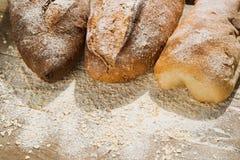 Variationer av bröd på överkanten av trätabellen med mjöl Arkivfoto